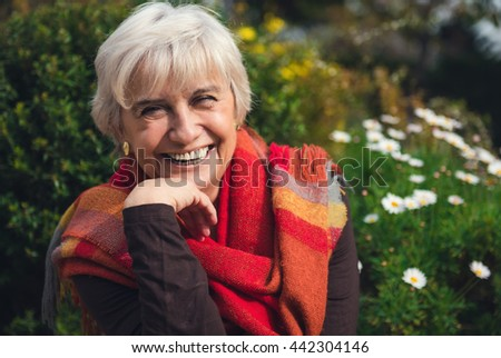 Cheerful mature woman laughing and showing happiness - stock photo