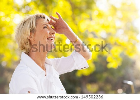 cheerful mature woman looking up outdoors - stock photo
