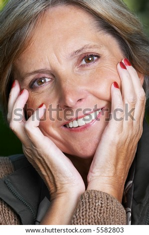 Cheerful mature woman looks at the camera