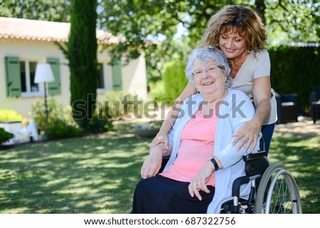 cheerful mature woman visiting her mother elderly senior female walk in retirement house hospital garden