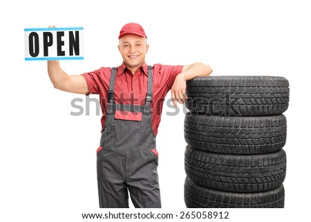 Cheerful mechanic holding an open sign and standing next to a stack of tires isolated on white background - stock photo