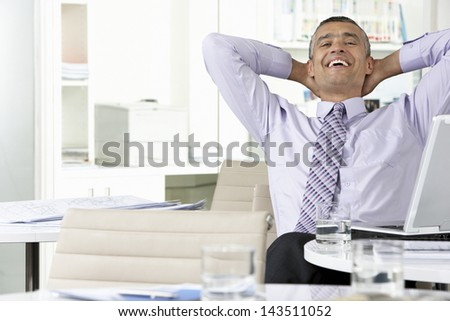Cheerful middle aged businessman relaxing with hands behind head at office desk - stock photo