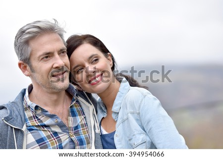Cheerful middle-aged couple embracing outside - stock photo