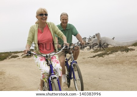 Cheerful middle aged couple riding bicycles along the beach - stock photo