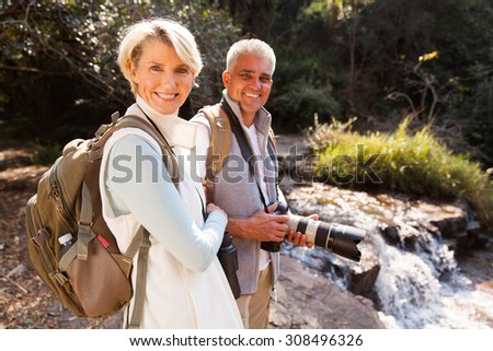 cheerful middle aged hikers relaxing by river enjoying outdoor activity  - stock photo