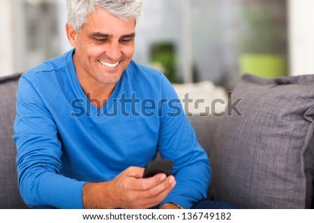 cheerful middle aged man reading emails on smart phone - stock photo