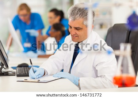 cheerful middle aged medical researcher working in lab - stock photo