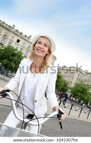 Cheerful middle aged woman riding bike in town - stock photo