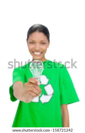 Cheerful model wearing recycling tshirt holding light bulb on white background - stock photo