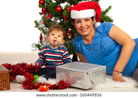 Cheerful mom and son under Xmas tree with presents - stock photo