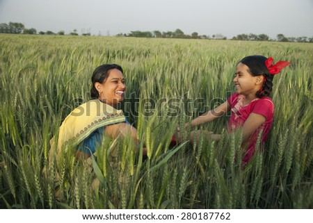 Cheerful mother and daughter playing in the wheat field - stock photo