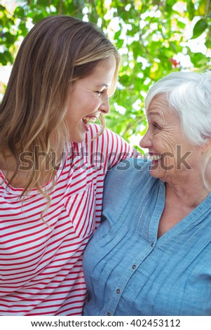 Cheerful mother and daughter with arm around while standing outdoors - stock photo