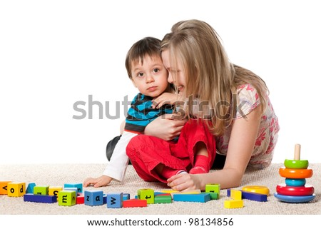 Cheerful mother and her little son are playing on the carpet with blocks - stock photo