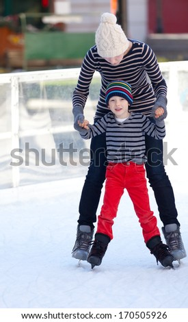 cheerful mother and her little son enjoying ice skating together at winter - stock photo