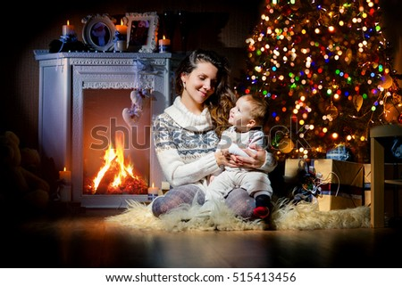 Cheerful mother and son at Christmas interior, fireplace, new year, christmas.