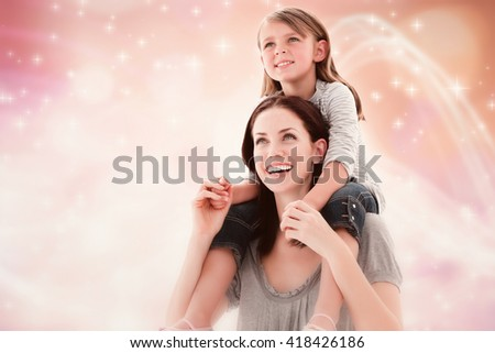 Cheerful mother giving piggyback ride to her daughter against glowing background - stock photo