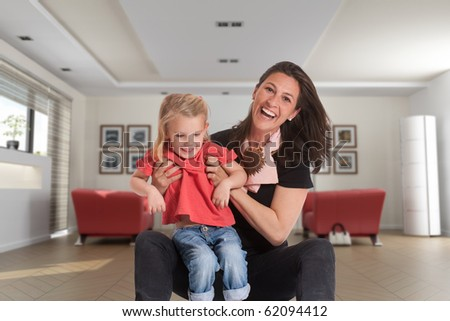 Cheerful mother holding a cute blonde little girl in a living room