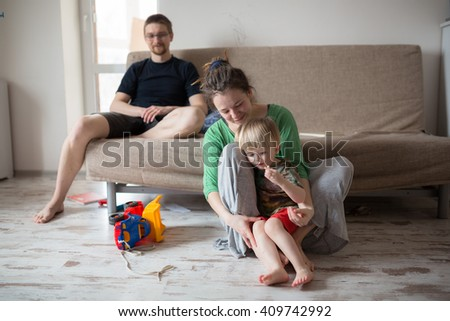 Cheerful mother is teaching toddler son, father near. She is holding him and sitting on flooring. The mom is looking at her child with love casual lifestyle photo series in real life interior - stock photo