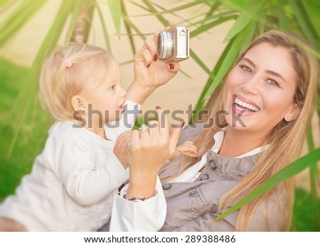 Cheerful mother photographing her precious adorable baby in the park for future memories, spending good time outdoors, happy family life