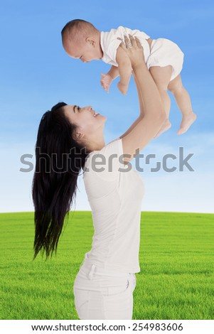 Cheerful mother playing together with her little baby on the meadow - stock photo