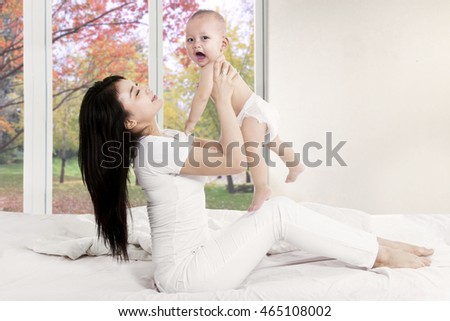 Cheerful mother playing with baby girl in bedroom with autumn background on the window