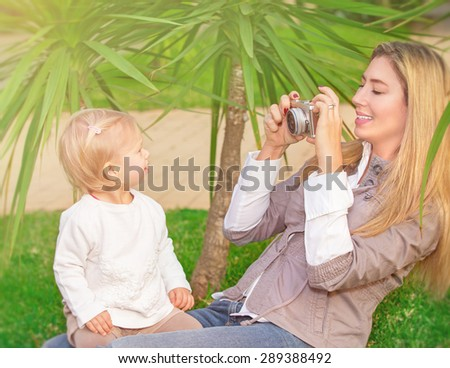 Cheerful mother taking picture of her cute little daughter in the park, happy young family having fun outdoors, parental love and enjoyment - stock photo
