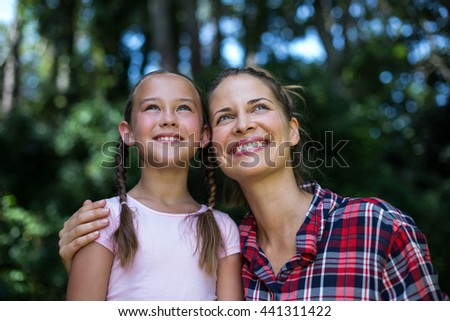 Cheerful mother with daughter looking up in back yard - stock photo