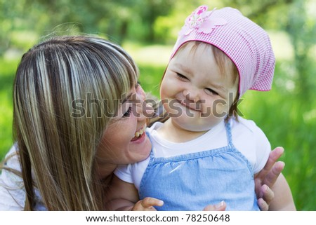 Cheerful mother with her daughter outdoor portrait - stock photo