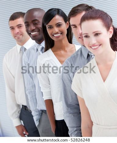 Cheerful multi-ethnic business partners standing in a line in the office