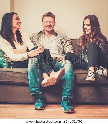 Cheerful multi-ethnic friends sitting on a sofa - stock photo