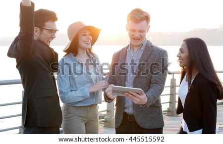 cheerful multi ethnic group of young friends having fun together outdoors at sunset. diverse team of business professionals looking at tablet computer screen talking chatting about new ideas   - stock photo