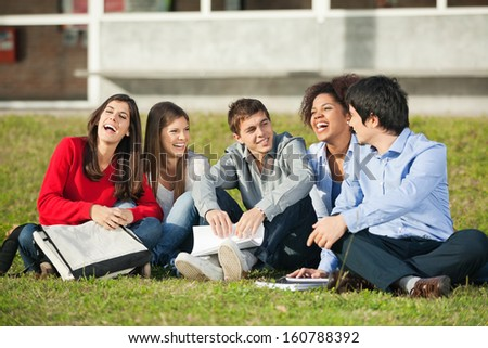 Cheerful multiethnic college students sitting on grass at campus - stock photo