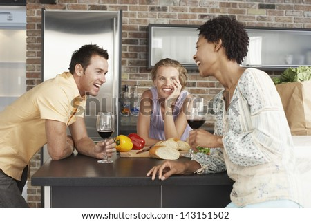 Cheerful multiethnic friends enjoying drinks at kitchen counter - stock photo