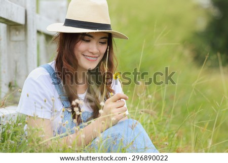 Cheerful multiracial Asian woman wearing a hat and  smelling flower in the grassland.   - stock photo