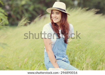 Cheerful multiracial Asian woman wearing a hat and  smelling flower in the grassland, warm tone - stock photo