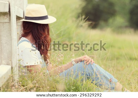 Cheerful multiracial Asian woman wearing a hat in the grassland, vintage tone - stock photo
