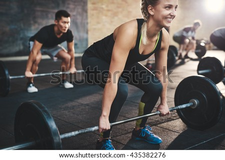 Cheerful muscular young woman with ponytail and black tights performing dead lift barbell exercises with other students - stock photo