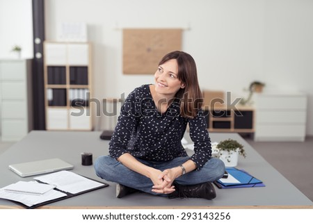 Cheerful Office Woman Sitting on the Boardroom Table with Legs Crossed While Looking Into Distance. - stock photo