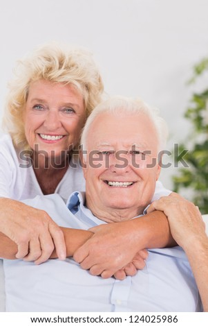 Cheerful old couple portrait hugging in the living room