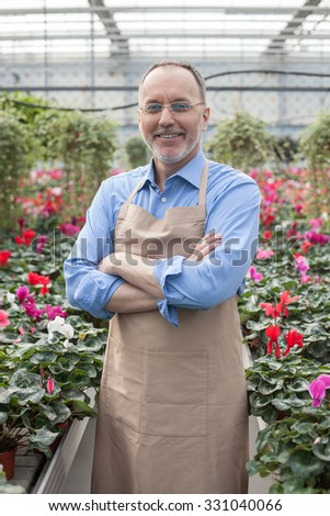 Cheerful old florist is standing at greenhouse. He crossed arms with confidence. The man is looking at camera and smiling. He is wearing apron and eyeglasses - stock photo