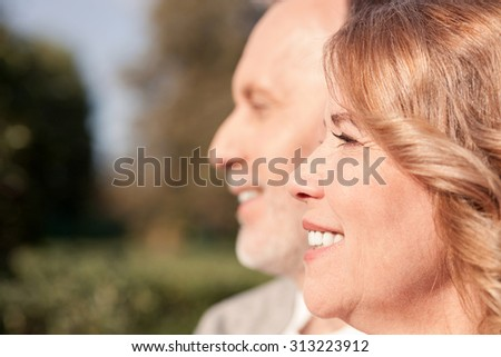 Cheerful old married couple are sitting in park and relaxing. They are looking forward with joy and smiling. Focus on their profile. Copy space in left side - stock photo