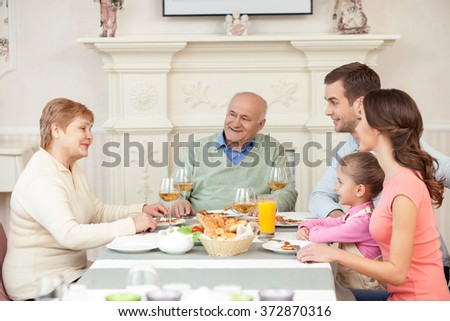 Cheerful old married couple is dining with their relatives - stock photo