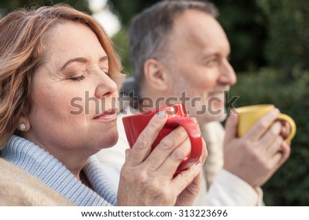 Cheerful old married couple is drinking hot tea. They are sitting on grass and smiling. The woman closed her eyes with relaxation - stock photo