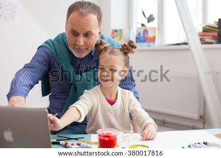 Cheerful old painter and his small granddaughter - stock photo