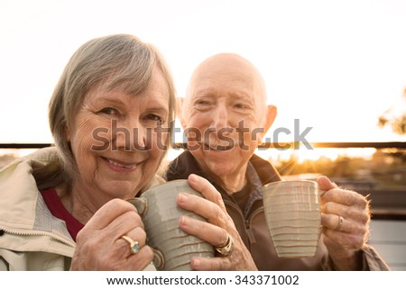 Cheerful older couple sitting outdoors with coffee - stock photo