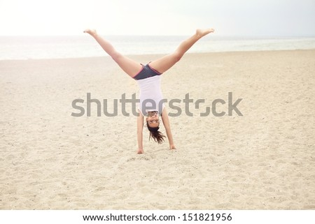 Cheerful outdoor woman on the beach doing a handstand - stock photo