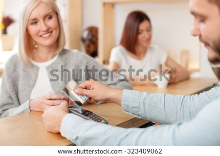 Cheerful owner of coffee shop is receiving payment from female client. He is standing and holding her credit card. The blond woman is looking at man and smiling. She is drinking coffee - stock photo