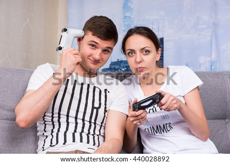 Cheerful pair playing video game while boy scratch his head by console sitting on the sofa at home - stock photo