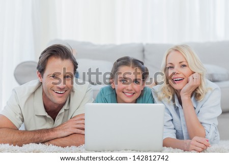 Cheerful parents and daughter using a laptop lying on a carpet - stock photo