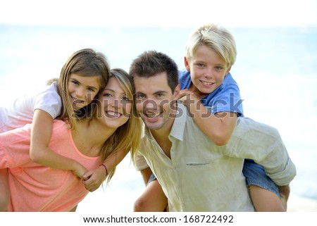 Cheerful parents holding kids on their back